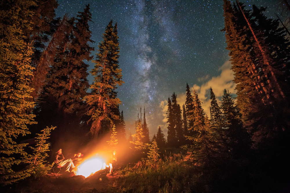 Family stargazing by a campfire, Colorado Rockies